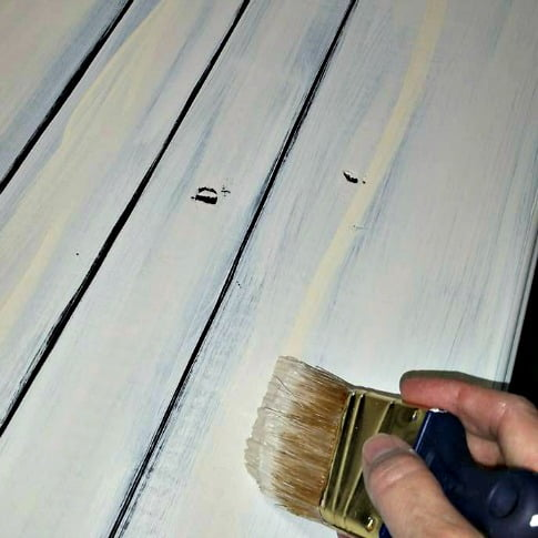 The next step is to paint over the stain on the faux plank farmhouse kitchen table to create a vintage painted look.