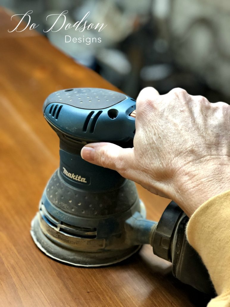 I use an orbital sander to gently scuff the wood before painting it.