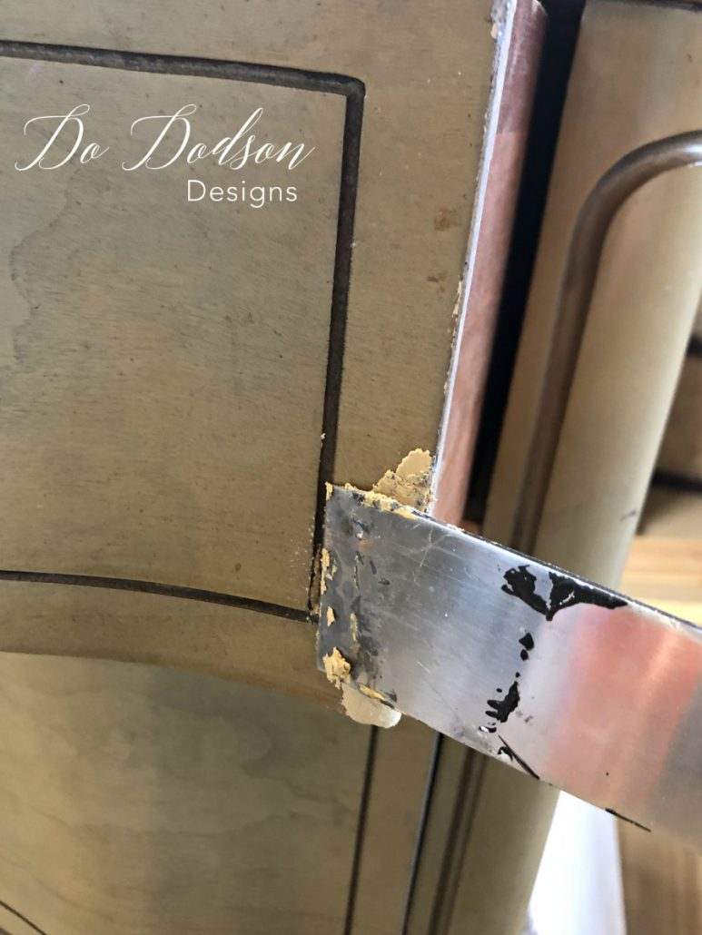 I apply to wood filler with a putty knife to the area with the missing veneer. #dododsondesigns #woodfiller #furniturerepair