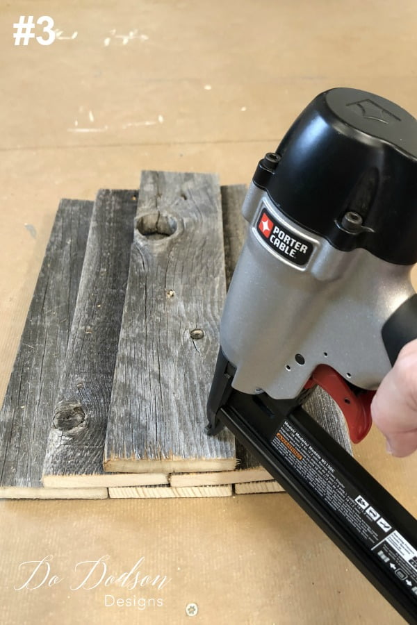 The #3 step for making DIY wood pumpkins is to stack the last board on top of the last 2 and them secure them using a stapler. Flip it over and continue securing the wood pumpkin with the staple gun from behind.