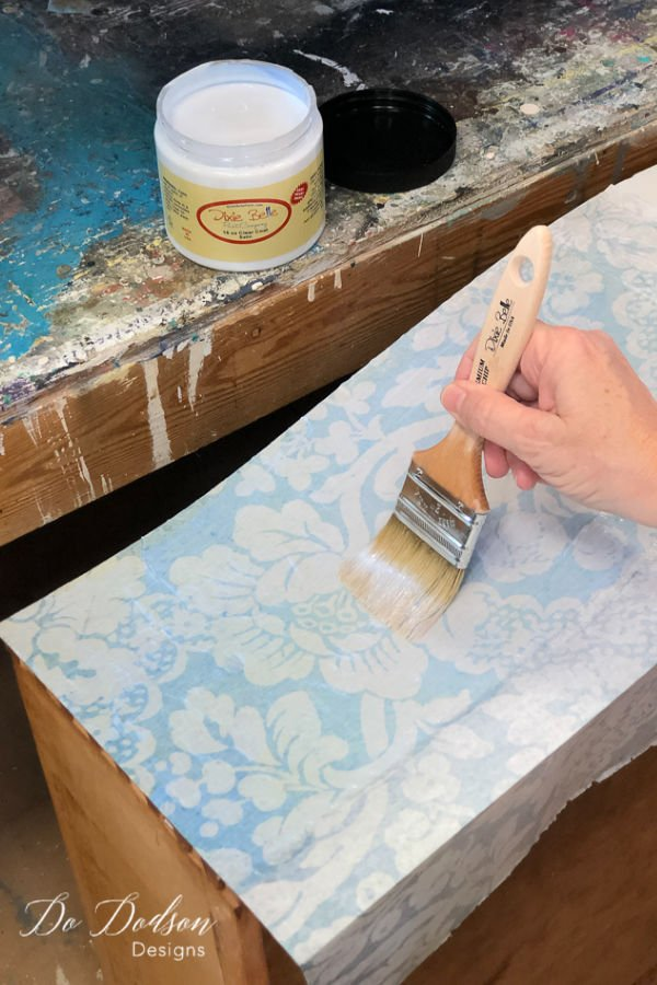 Add another layer of the top coat over the decoupage tissue paper on your wood furniture as a sealer.
