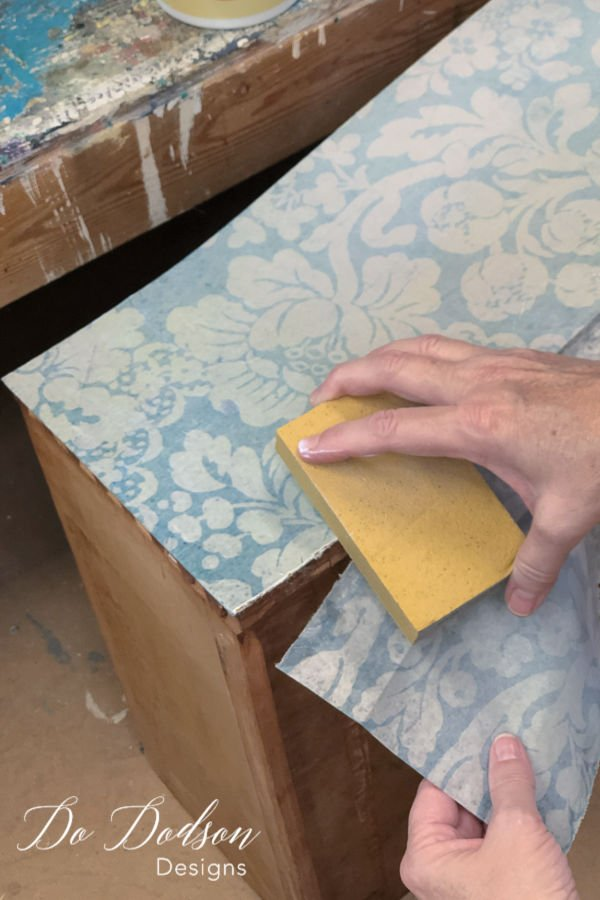 While the top coat is still wet, use a fine grit sanding block to carefully trim the extra decoupage paper away.
