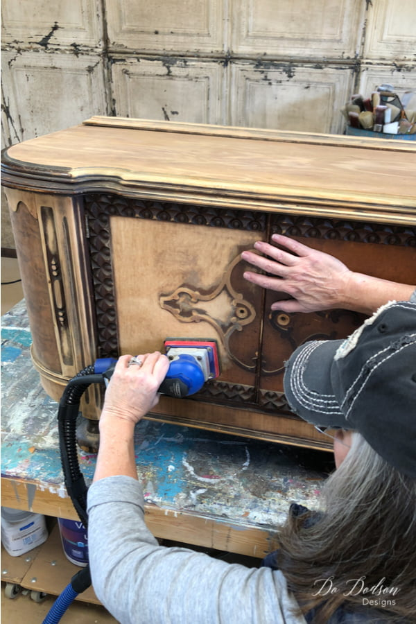 I started this furniture makeover by sanding down the old varnish to reveal all the beautiful wood. The black wax will compliment the wood nicely.