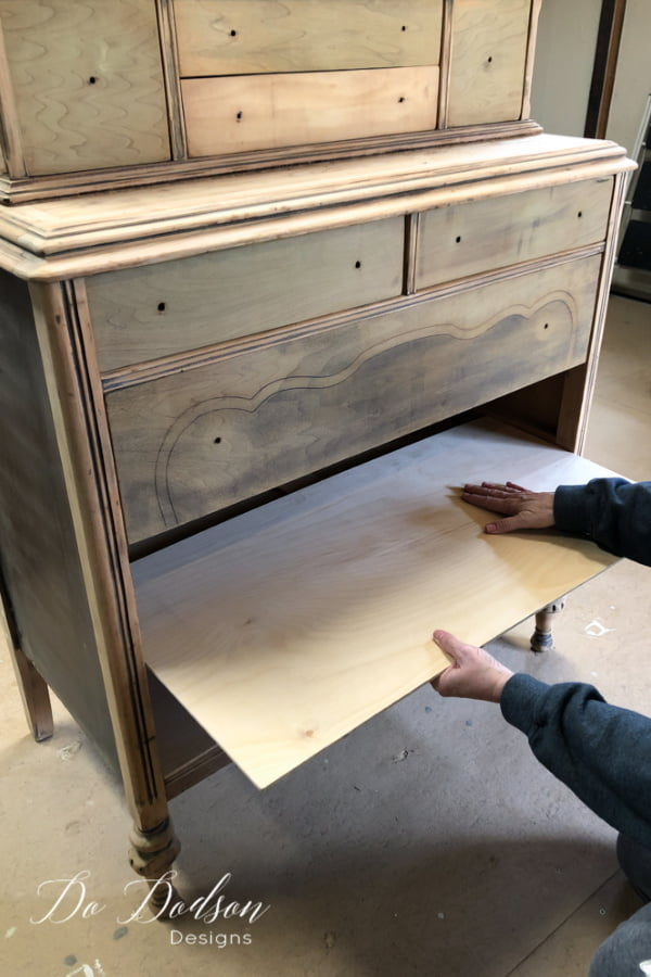 After cutting and sanding the raw wood edges, insert the plywood pieces into the slots inside the wood drawer openings. This can be a bit tricky to fit sometimes so it may take a little finesse. Working with these tight spaces in a dresser can be a challenge but well worth the extra fuss.when adding shelves to a dresser.