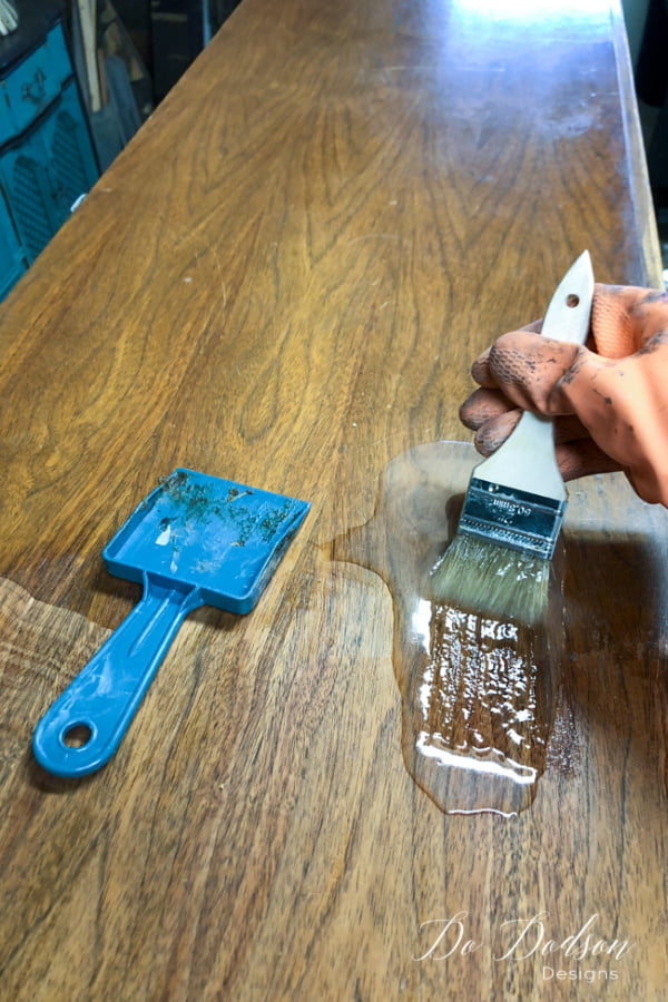 Apply a liberal amount of the gel stripper with a disposable paintbrush. Wait the listed time recommended on the product and test the area by gently scrapping back the old finish in the direction of the wood grain.
