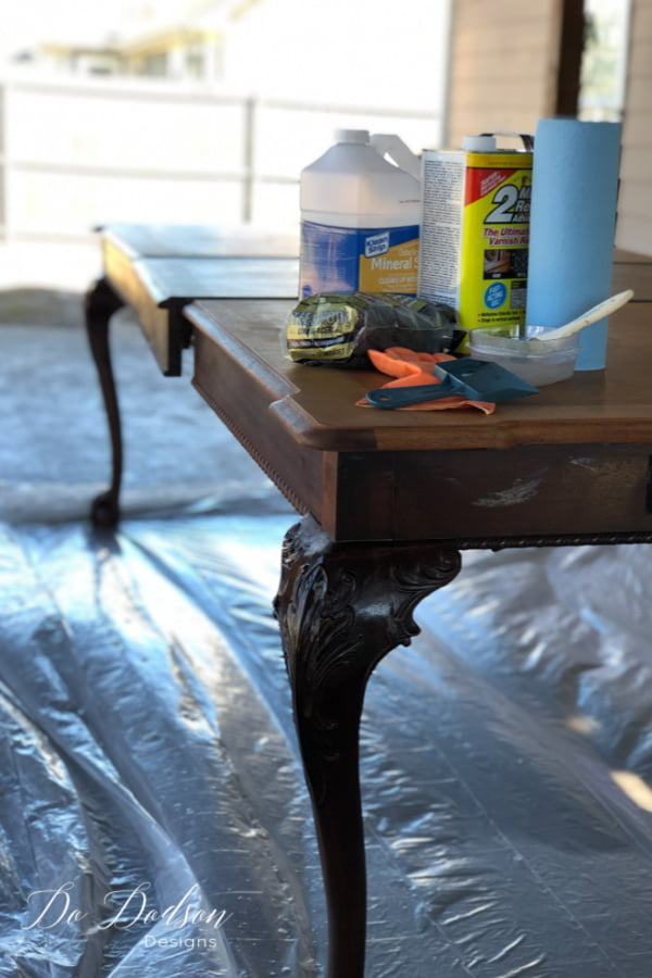 Before whitewashing a wood table, you'll need a chemical stripper to reveal the beautiful raw wood of the table top.