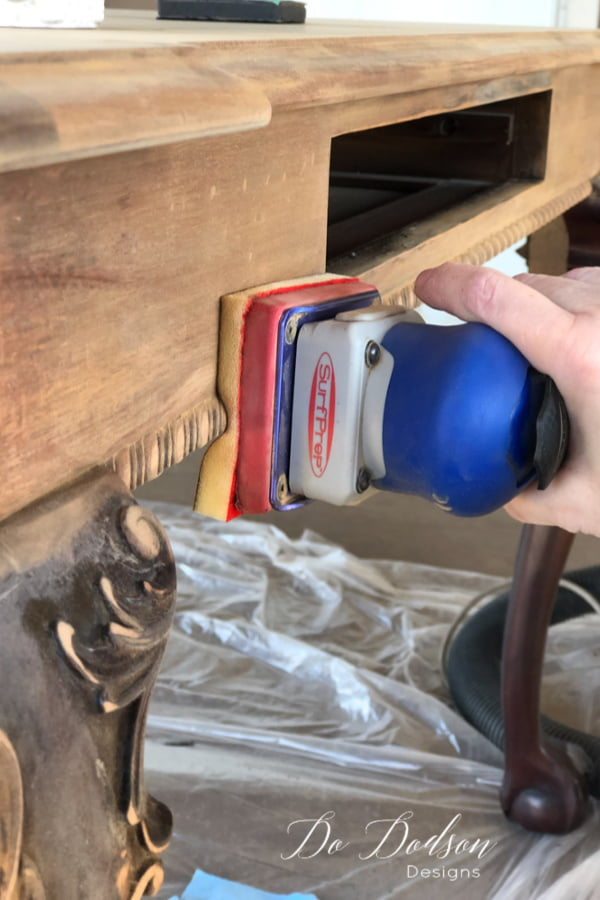 Next, sand the wood to remove any leftover varnish. I use a sander that has padded sandpaper that's great for getting into the detailed wood trim and carvings. Clean the wood after sanding with a 50/50 mixture of denatured alcohol and water. The whitewash I'm using on the table top will look amazing!