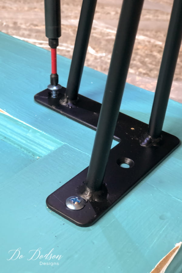 Secure the hairpin legs with screws. Be sure and pre-drill the holes to prevent cracking and splitting of the wood door.