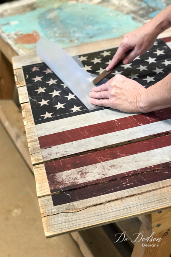 Of course, I could have just painted this American flag pallet sign but I found this transfer and I wanted to try it on a pallet. I have used them on painted furniture and they work great so I was ready to find out how well it would stick to a rough surface. The application is simple... peel off the backing and rub it on. This transfer came in two pieces so be sure to measure where you want it before applying the sticky side to the wood.