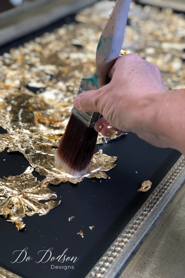 Use a soft bristle paint brush to gently smooth the gold leaf onto the tacky adhesive. This can be tricky but so worth the results!