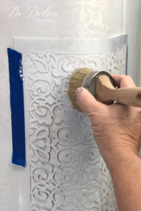 Here is the fun part! Use 2 colors that are similar (I used Cotton and Sandbar) and apply the chalk paint like you would over any stencil using a flat natural bristle brush. I call this technique dabbing. Apply the chalk mineral paint sparingly using an up and down motion, never back and forth. As you dab the chalk paint over the stencil you will need to add the two colors in different areas and overlap them.