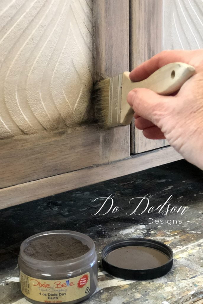 Adding aging dust to the corners of this cabinet dresser gave it more of a cohesive feel. It transitioned the textured wallpaper nicely on this furniture makeover.