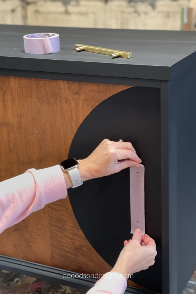 And lastly, place the painter's tape where you want the hardware to go on your dresser/cabinet. Mark the holes through the tape and proceed with drilling the perfect placement for your new hardware.