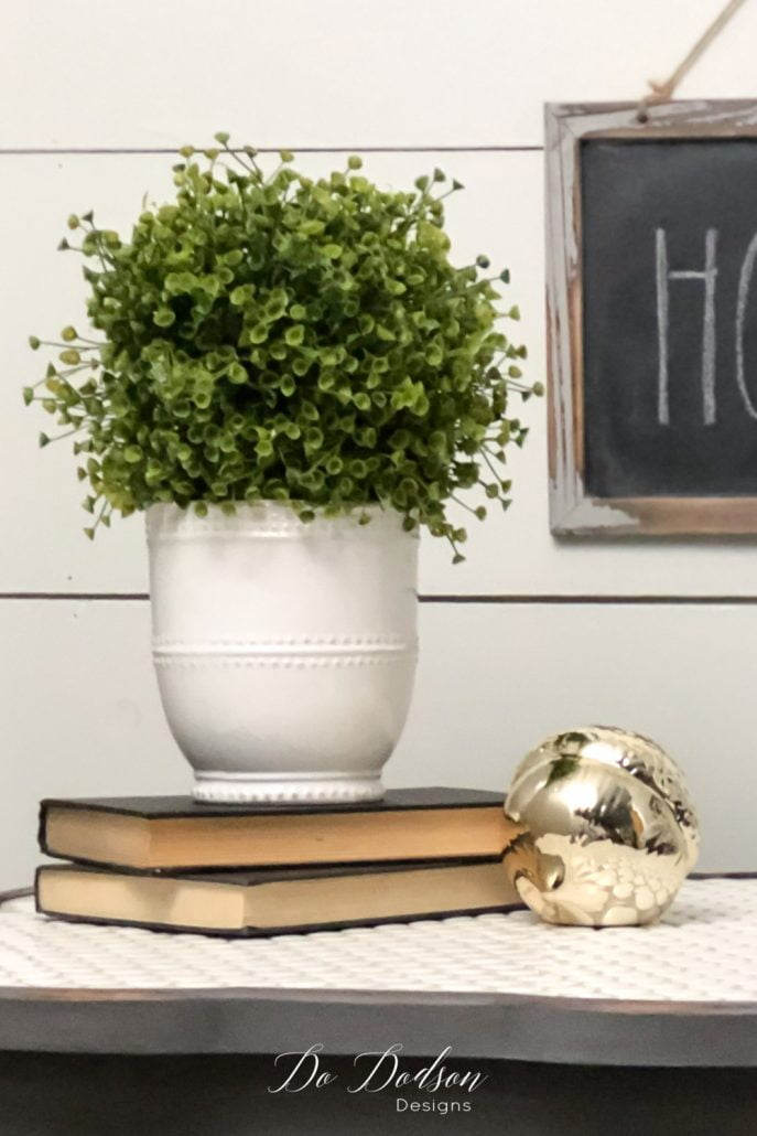 The visual triangle design is also found here using books. Try using books as a riser for the vase to give it more height, and then add a small item beside it. Simple and not overdone; classy, clean lines.