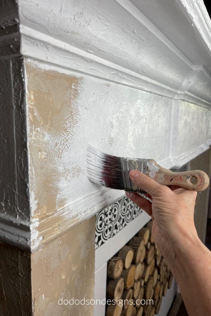 After adding the texture paint to my builder-grade fireplace mantel, I painted over the whole thing with a white chalk paint. Now, when I sand it back, I'll get a DIY chipped paint look. You got to see the finished product! It's so cool!