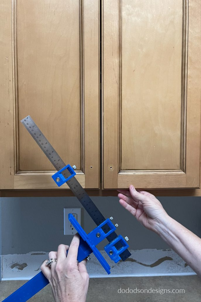 I used a cabinet hardware jig to get the perfect placement of my new kitchen cabinet hardware. Long modern pulls are perfectly aligned.