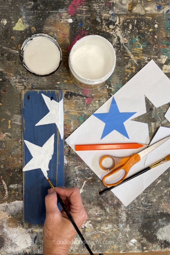 If you have a computer, create a word document and insert a star shape. Print it off on paper and cut it out with a pair of scissors. Lay the cut out of the star over your wooden firecrackers and trace around it with a pencil. I like using paper to make these simple stencils because it wraps around the sides easily.