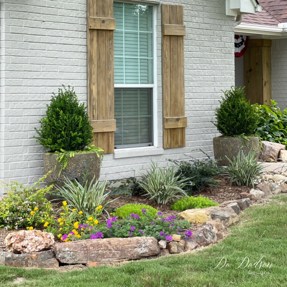 I love the look of painted brick with the warm wood tones and those rock borders in the flower beds make the natural elements cohesive.