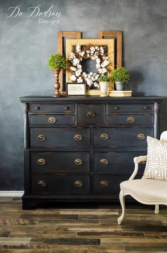 Check out the lovely distressed look on this masculine black painted dresser! Learn how to distress your chalk-painted furniture with less effort.