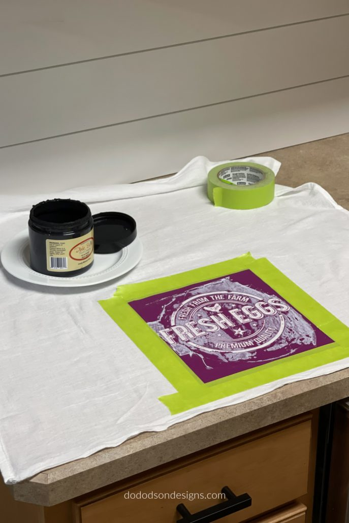 Remove the silk screen stencil backing (save for later) and place the sticky side down on the flour sack towel. I like to use painter's tape to add a border around the stencil to protect the fabric from runaway paint.