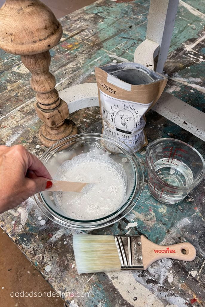 Mix the milk paint powder with water in a bowl and stir, stir, stir! It will be a little lumpy but that's okay. Get all the details of this chippy paint finish for wood furniture over on my blog.